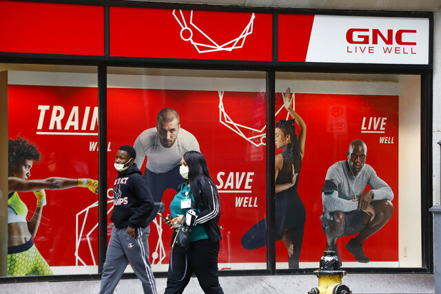 FILE- In this April 29, 2020 file photo, a couple walks past a GNC store at the company's world headquarters in downtown Pittsburgh. The outbreak of the coronavirus has dealt a shock to the global economy with unprecedented speed. Health and wellness company GNC Holdings has filed for Chapter 11 bankruptcy protection and is looking to close at least 800 to 1,200 stores. (AP Photo/Gene J. Puskar, File)