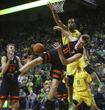 Oregon State's Zach Reichle, center, is fouled as he goes to the basket between teammate Kyle Kelley, left, and Oregon's Paul White, right, during the second half of an NCAA college basketball game Saturday, Jan. 5, 2019, in Eugene, Ore. (AP photo/Chris Pietsch)
