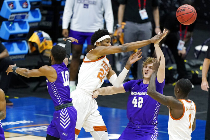 Texas' Kai Jones (22) passes the ball over Abilene Christian's Clay Gayman (42) during the first half of a college basketball game in the first round of the NCAA tournament at Lucas Oil Stadium in Indianapolis Saturday, March 20, 2021. (AP Photo/Mark Humphrey)
