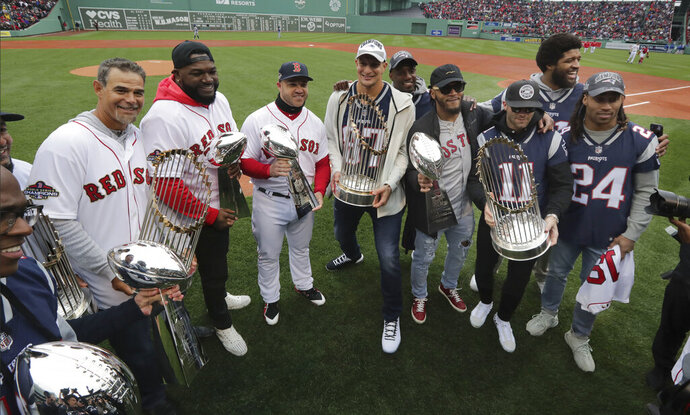 New England Patriots and Boston Red Sox players hold Super Bowl and World Series trophies before the home opener baseball game between the Red Sox and the Toronto Blue Jays, Tuesday, April 9, 2019, in Boston. From left they are, Patriots' Matthew Slater, Red Sox's Mike Lowell, David Ortiz and Steve Pearce, Patriots' Rob Gronkowski, Patrick Chung, Julian Edelman, and Stephon Gilmore (24). At rear are Duron Harmon, behind Gronkowski, and New England Patriots' Deatrich Wise, behind Edelman. (AP Photo/Charles Krupa)