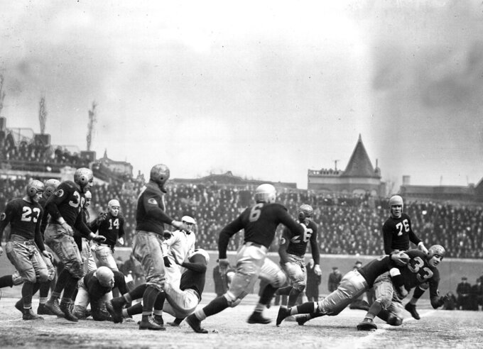 FILE - In this Dec. 12, 1937, file photo, Washington Redskins quarterback Sammy Baugh (33) is brought down after a gain, by the Chicago Bears during an NFL football Championship game on a frozen Wrigley Field in Chicago. The Redskins won 28-21. (AP Photo/File)
