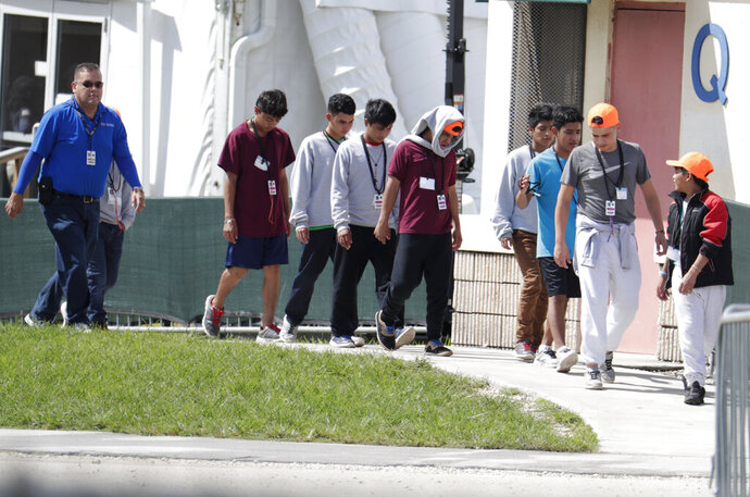 Migrant children walk on the grounds of the Homestead Temporary Shelter for Unaccompanied Children, Monday, July 15, 2019, in Homestead, Fla. (AP Photo/Lynne Sladky)