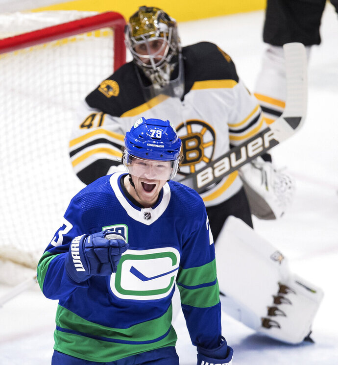 Vancouver Canucks' Tyler Toffoli, front, celebrates his first goal against Boston Bruins goalie Jaroslav Halak, of Slovakia, during the third period of an NHL hockey game Saturday, Feb. 22, 2020, in Vancouver, British Columbia. (Darryl Dyck/The Canadian Press via AP)