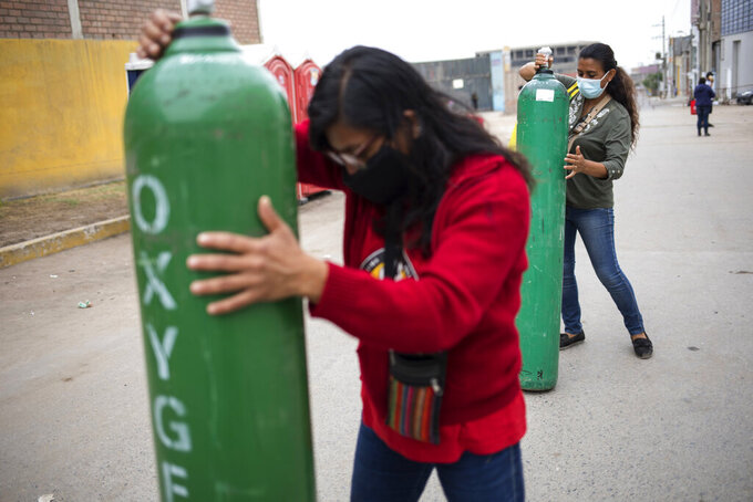 Marlene and Rosalyn Del Aguila roll tanks filled with oxygen to a waiting car, to deliver to their mother who has tested positive for COVID-19, in the Villa El Salvador neighborhood of Lima, Peru, Wednesday, April 7, 2021, amid the new coronavirus pandemic. (AP Photo/Rodrigo Abd)