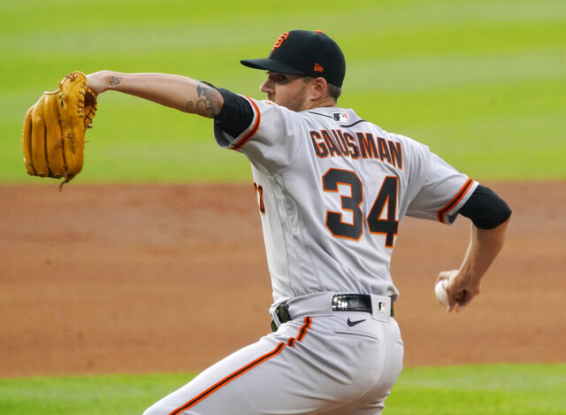 FILE - In this Aug. 4, 2020, file photo, San Francisco Giants starting pitcher Kevin Gausman throws against the Colorado Rockies during the first inning of a baseball game in Denver. Gausman and Mets pitcher Marcus Stroman accepted $18.9 million qualifying offers Wednesday, Nov. 11, receiving one-year deals to stay with their teams rather than test what they could get in free agency. (AP Photo/Jack Dempsey, File)