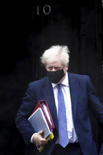 Britain's Prime Minister Boris Johnson leaves 10 Downing Street to attend the parliament Prime Minister's Questions, at the Houses of Parliament in London, Wednesday Oct. 21, 2020.  The government imposed highly restrictive Tier 3 restrictions on the northern England region of Greater Manchester on Tuesday after failing to reach agreement with local authorities. (Stefan Rousseau/PA via AP)