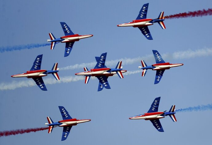 French aircrafts of the Patrouille de France spray colored smoke during a performance on the opening day of the Dubai Airshow in Dubai, United Arab Emirates, Sunday, Nov. 17, 2019. (AP Photo/Kamran Jebreili)