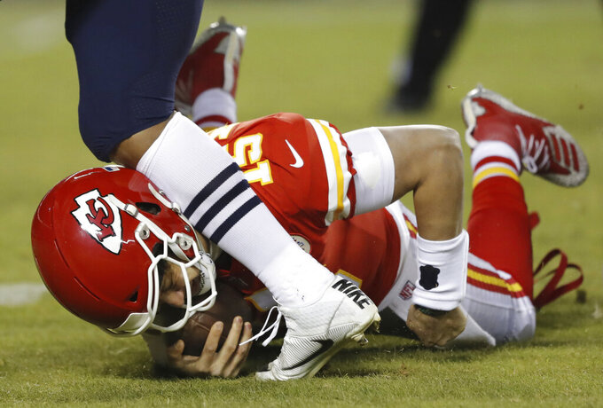 A player runs into Kansas City Chiefs quarterback Patrick Mahomes (15) after Mahomes was sacked by New England Patriots middle linebacker Kyle Van Noy during the first half of the AFC Championship NFL football game, Sunday, Jan. 20, 2019, in Kansas City, Mo. (AP Photo/Charlie Neibergall)