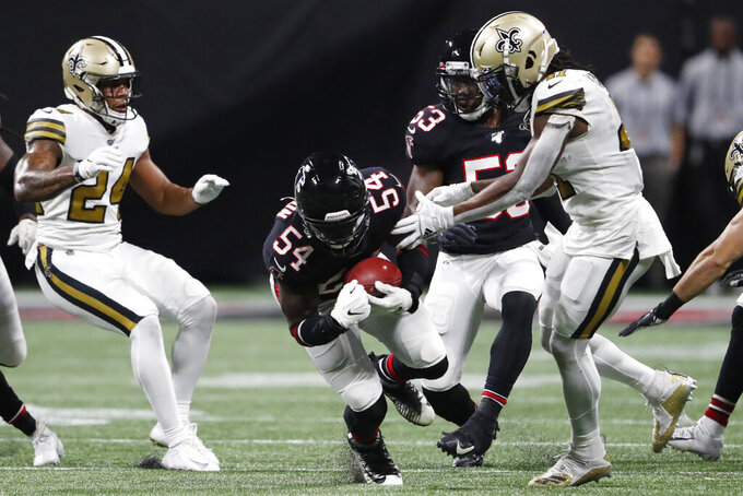 Atlanta Falcons linebacker Foye Oluokun (54) picks up an onside kick against the New Orleans Saints during the second half of an NFL football game, Thursday, Nov. 28, 2019, in Atlanta. (AP Photo/John Bazemore)