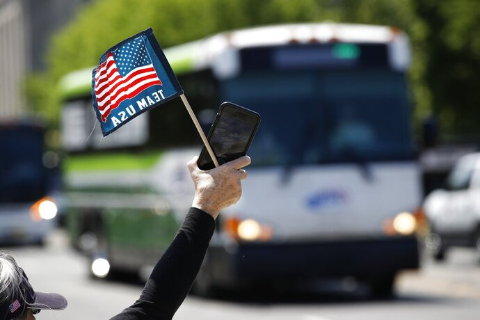 FILE - In this May 13, 2020, file photo, tour guide Barbara Western waves a flag in support of bus and motor coach operators circling National Mall in Washington during a rally to raise awareness of the industry in the wake of the coronavirus outbreak. America's private buses are ground to a halt, and members of the industry say they need federal assistance to help the country get back to work and play. (AP Photo/Patrick Semansky, File)