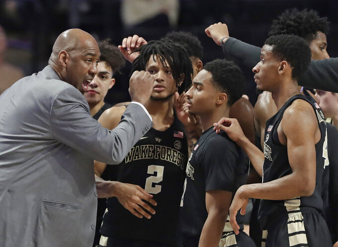 Wake Forest head coach Danny Manning, left, talks to his team during a timeout in the first half of an NCAA college basketball game against Miami in Winston-Salem N.C., Tuesday, Feb. 26, 2019. (AP Photo/Chuck Burton)
