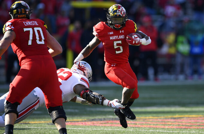 Maryland running back Anthony McFarland (5) runs the ball against Ohio State defensive tackle Haskell Garrett (92) during the first half of an NCAA football game, Saturday, Nov. 17, 2018, in College Park, Md. Also seen is Maryland offensive lineman Sean Christie (70). (AP Photo/Nick Wass)