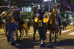 Police on horseback move people back as rowdy fans celebrate, Sunday, Oct. 11, 2020, in Los Angeles, after the Los Angeles Lakers defeated the Miami Heat in Game 6 of basketball's NBA Finals to win the championship. (AP Photo/Jintak Han)