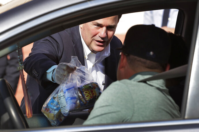 FILE - In this March 19, 2020, file photo Gov. Doug Ducey, left, hands a bag of food to a student outside Sunset Elementary School in Phoenix. Citing the state's surge of COVID-19 cases, Arizona's top education official on Saturday, Jan. 2, 2021, called for Ducey to order that public schools use only distance learning for the next two weeks without waivers from health officials. (AP Photo/Matt York, File)