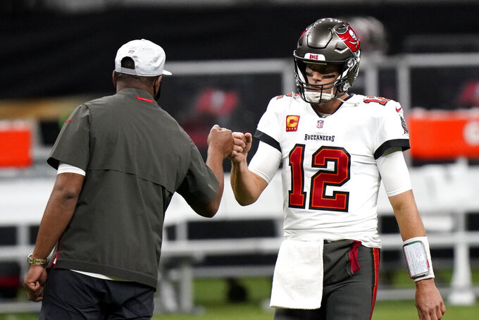 Tampa Bay Buccaneers quarterback Tom Brady (12) fist bumps with a coach before the first half of an NFL divisional round playoff football game between the New Orleans Saints and the Tampa Bay Buccaneers, Sunday, Jan. 17, 2021, in New Orleans. (AP Photo/Brynn Anderson)