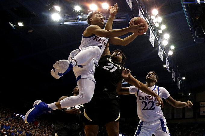 Kansas' Devon Dotson, left, shoots under pressure from Colorado's Evan Battey (21) during the first half of an NCAA college basketball game Saturday, Dec. 7, 2019, in Lawrence, Kan. (AP Photo/Charlie Riedel)