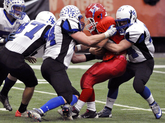 FILE- In this Nov. 24, 2012 file photo, Hornell's Luke Morgan is wrapped up by Hoosick Falls defenders during the third quarter of the New York State High School Football Class C championship game in Syracuse, N.Y. On Wednesday, Sept. 9, 2020, the New York State Public High School Athletic Association announced that football, volleyball and competitive cheer fall seasons will be postponed until March to address concerns associated with COVID-19. (AP Photo/Kevin Rivoli, File)