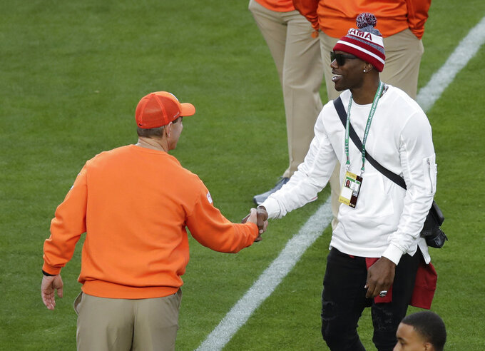 Clemson head coach Dabo Swinney talks to Terrell Owens before the NCAA college football playoff championship game against Alabama Monday, Jan. 7, 2019, in Santa Clara, Calif. (AP Photo/Jeff Chiu)