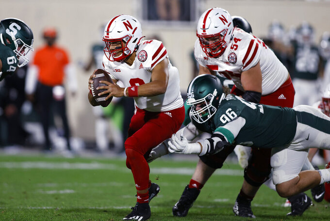 Nebraska quarterback Adrian Martinez (2) escapes from Michigan State's Jacub Panasiuk (96) and Jacob Slade, left, during the second quarter of an NCAA college football game, Saturday, Sept. 25, 2021, in East Lansing, Mich. (AP Photo/Al Goldis)
