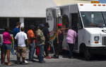 People line up to buy pre-paid cell phone cards, for sale from a mobile Aliv office, after the passing of Hurricane Dorian in Freeport, Bahamas, Wednesday, Sept. 11, 2019. While power has returned to much of Grand Bahama, spokesman Carl Smith for the country's emergency management Agency said the electrical infrastructure around Marsh Harbour, Abaco's largest city, was destroyed. (AP Photo/Ramon Espinosa)