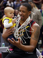 Cleveland Cavaliers' Channing Frye holds his daughter after an NBA basketball game against the Charlotte Hornets, Tuesday, April 9, 2019, in Cleveland. Frye is retiring after 13 seasons. Charlotte won 124-97. (AP Photo/Tony Dejak)