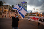 An Israeli protester wearing face masks amid concerns over the country's coronavirus outbreak holds an Israeli flag as others carry a banner showing Israeli Prime Minister Benjamin Netanyahu during