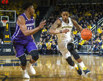 Northwestern guard Anthony Gaines (11) defends Michigan guard Charles Matthews, right, in the second half of an NCAA college basketball game in Ann Arbor, Mich., Sunday, Jan. 13, 2019. Michigan won 80-60. (AP Photo/Tony Ding)