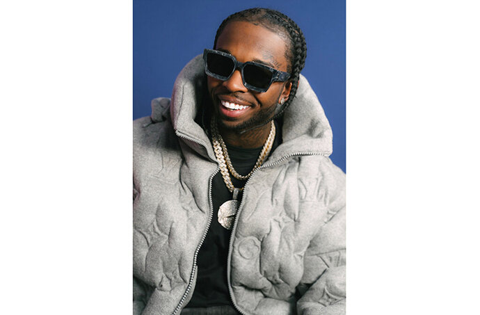FILE - This image released by Republic Records shows rapper Pop Smoke. Authorities believe the rising rapper, whose legal name is Bashar Barakah Jackson, was shot and killed during a Los Angeles home-invasion robbery in February after his social media posts led five suspects to the house he was renting. Prosecutors say two men and two teens have been charged in the death of the rapper. Los Angeles District Attorney Jackie Lacey said in a statement Monday, July 13, 2020, that Corey Walker and Keandre Rodgers were charged with a murder that occurred during the commission of a robbery and burglary. The two male teens were also charged with murder and robbery in juvenile court. (Tracy Awino/Republic Records via AP)