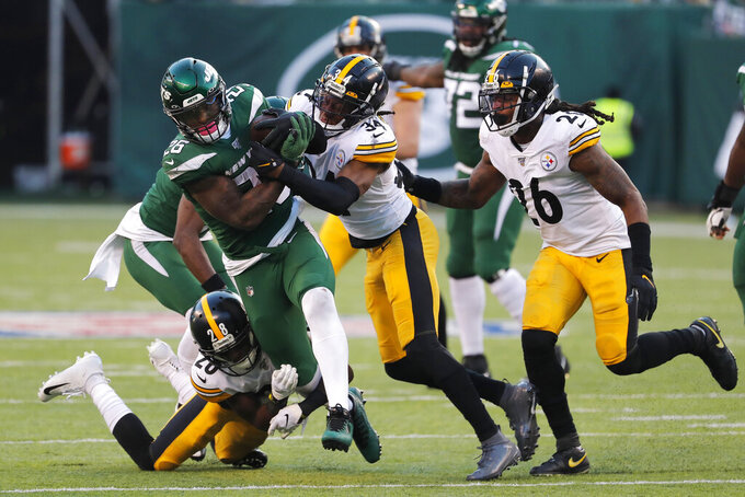 New York Jets running back Le'Veon Bell (26) is stopped by Pittsburgh Steelers strong safety Terrell Edmunds (34) and Pittsburgh Steelers cornerback Mike Hilton (28) in the second half of an NFL football game, Sunday, Dec. 22, 2019, in East Rutherford, N.J. (AP Photo/Seth Wenig)