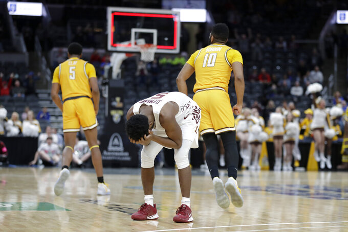 Valparaiso's Donovan Clay, left, and Eron Gordon (10) celebrate as Loyola of Chicago's Keith Clemons, center, reacts following an NCAA college basketball game in the quarterfinal round of the Missouri Valley Conference men's tournament Friday, March 6, 2020, in St. Louis. Valparaiso won 74-73 in overtime. (AP Photo/Jeff Roberson)