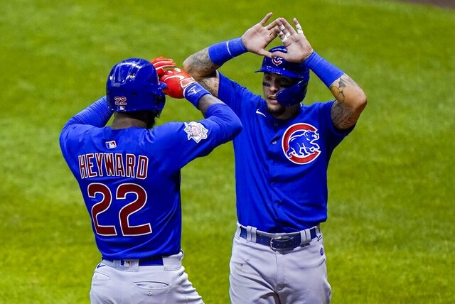 Chicago Cubs' Jason Heyward is congratulated by Javier Baez after hitting a three-run home run during the ninth inning of a baseball game against the Milwaukee Brewers Saturday, Sept. 12, 2020, in Milwaukee. (AP Photo/Morry Gash)