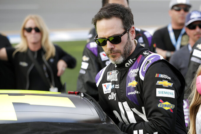 FILE - In this Feb. 16, 2020 file photo Jimmie Johnson climbs intp his car before the NASCAR Daytona 500 auto race at Daytona International Speedway in Daytona Beach, Fla.   (AP Photo/John Raoux, File)