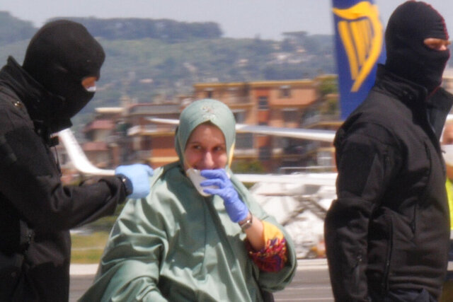 In this image taken from a video, Silvia Romano is flanked by two masked security officers as she walks on the tarmac after landing at Rome's Ciampino airport, Sunday, May 10, 2020. Wearing a surgical mask, disposable gloves and booties to guard against COVID-19, a young Italian woman has returned to her homeland after 18 months as a hostage in eastern Africa. (AP Photo/Paolo Santalucia)