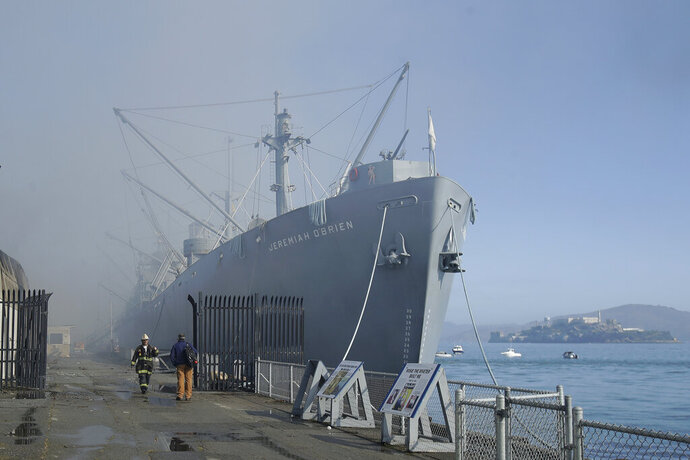 Fire officials stand in front of the SS Jeremiah O'Brien ship after a fire broke out before dawn at Fisherman's Wharf in San Francisco, Saturday, May 23, 2020. A warehouse was destroyed. Fire officials said no injuries have been reported Saturday morning and firefighters are making multiple searches to ensure no one was inside the building on Pier 45. (AP Photo/Jeff Chiu)