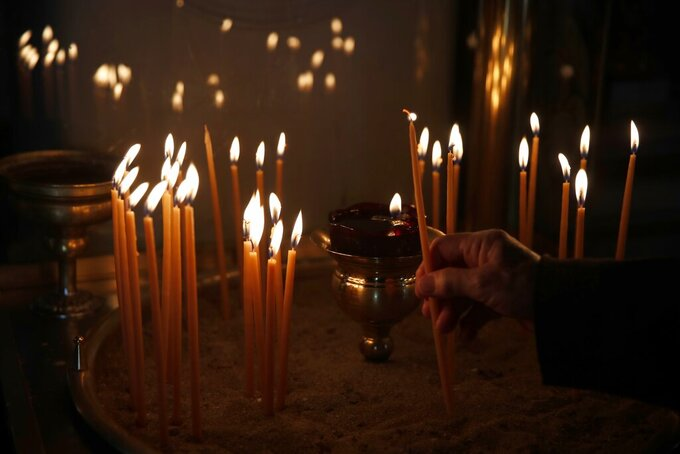 A woman lights a candle inside the Agios Nikolaos church, in Halandri suburb, northern Athens, Tuesday, April 27, 2021. During the Holy Week churches will be allowed to operate with a severely reduced capacity with attendees, and the ratio of one person per 25 square meters will be applied during services, among other measures. (AP Photo/Thanassis Stavrakis)