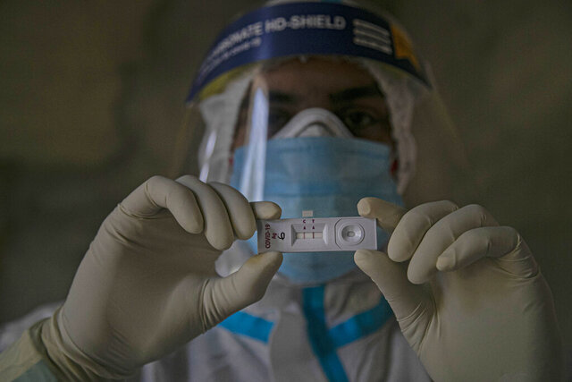 A health worker displays a test kit showing a positive result for COVID-19 in Gauhati, India, Friday, Sept. 18, 2020. India's coronavirus cases jumped by another 96,424 in the past 24 hours, showing little sign of leveling. India is expected to have the highest number of confirmed cases within weeks, surpassing the United States, where more than 6.67 million people have been infected. (AP Photo/Anupam Nath)
