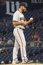 Arizona Diamondbacks starting pitcher Madison Bumgarner looks at a new baseball after giving up a home run to Pittsburgh Pirates' Michael Chavis during the third inning of a baseball game Tuesday, Aug. 24, 2021, in Pittsburgh. (AP Photo/Keith Srakocic)