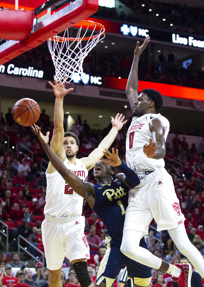 Pittsburgh's Xavier Johnson (1) attempts a shot between North Carolina State's Devon Daniels, left, and North Carolina State's DJ Funderburk (0) during the second half of an NCAA college basketball game in Raleigh, N.C., Saturday, Jan. 12, 2019. (AP Photo/Ben McKeown)