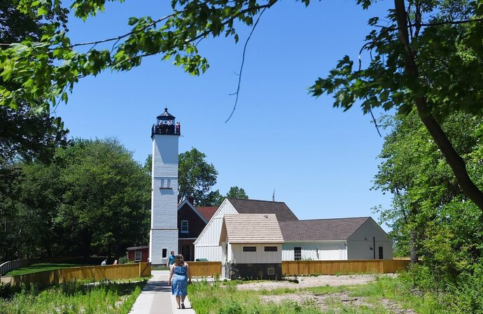 In this July 7, 2018 photo, visitors tour the Presque Isle Lighthouse at Presque Isle State Park near Erie, Pa. Attendance is up markedly at Presque Isle Lighthouse, said Michael Sullivan, executive director of the lighthouse located near Beach 9. (Jack Hanrahan/Erie Times-News via AP)