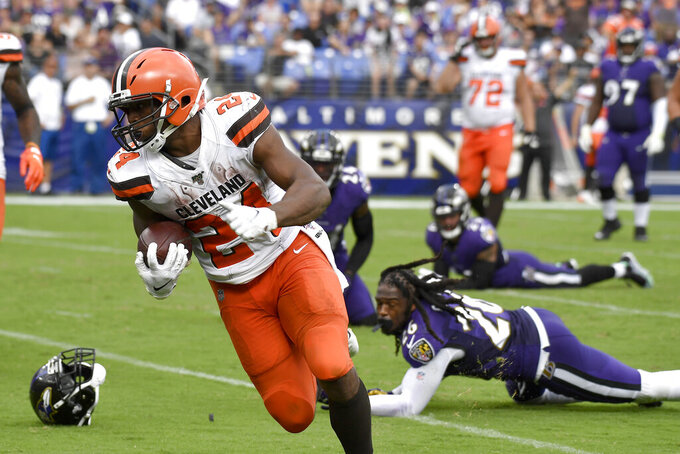 Cleveland Browns running back Nick Chubb (24) prepares to cross the goal line after avoiding several tackles from Baltimore Ravens defenders during the second half of an NFL football game Sunday, Sept. 29, 2019, in Baltimore. (AP Photo/Brien Aho)