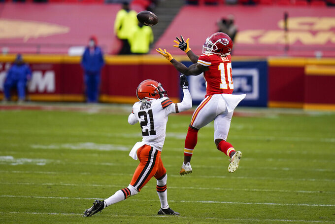 Kansas City Chiefs wide receiver Tyreek Hill (10) catches a pass over Cleveland Browns cornerback Denzel Ward (21) during the second half of an NFL divisional round football game, Sunday, Jan. 17, 2021, in Kansas City. (AP Photo/Jeff Roberson)