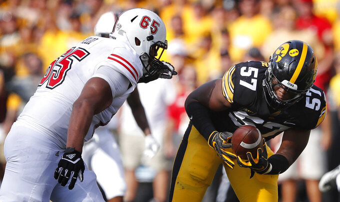 Iowa defensive end Chauncey Golston (57) recovers a fumble in front of Northern Illinois offensive lineman Nathan Veloz, left, during the second half of an NCAA college football game, Saturday, Sept. 1, 2018, in Iowa City, Iowa. Iowa won 33-7. (AP Photo/Charlie Neibergall)