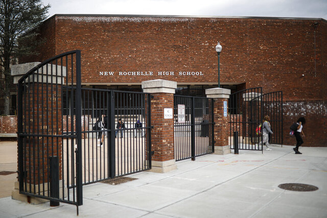 Students leave New Rochelle High School after classes are dismissed, Tuesday, March 10, 2020, in New York. State officials are shuttering schools and houses of worship for two weeks in part of the New York City suburb New Rochelle and sending the National Guard there to help respond to what appears to be the nation's biggest cluster of coronavirus cases. (AP Photo/John Minchillo)