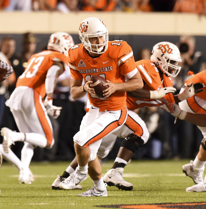 Oklahoma State quarterback Taylor Cornelius looks for an open teammate in the second half of an NCAA college football game in Stillwater, Okla., Saturday, Oct. 27, 2018. Cornelius threw for 321 yards in the Oklahoma State 38-35 win over Texas.(AP Photo/Brody Schmidt)