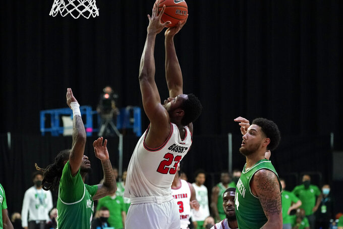 Western Kentucky center Charles Bassey, center, shoots between North Texas guard James Reese, left, and forward Zachary Simmons, right, during the second half of the championship game in the NCAA Conference USA men's basketball tournament Saturday, March 13, 2021, in Frisco, Texas. (AP Photo/Tony Gutierrez)