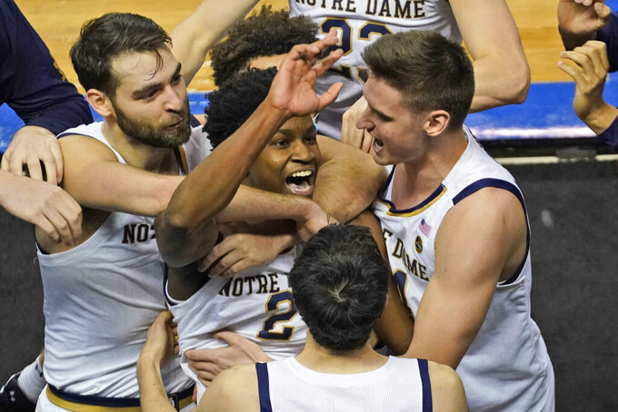 Notre Dame guard Trey Wertz (2) who sank the game-winning shot is swarmed by teammates after their 80-77 win over Wake Forest in the first round of the Atlantic Coast Conference tournament in Greensboro, N.C., Tuesday, March 9, 2021. (AP Photo/Gerry Broome)