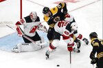 Boston Bruins' Charlie Coyle (13) battles New Jersey Devils' Sami Vatanen (45) in front of Devils goalie Cory Schneider (35) during the second period of an NHL hockey game in Boston, Saturday, Oct. 12, 2019. (AP Photo/Michael Dwyer)