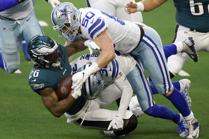 Philadelphia Eagles running back Miles Sanders (26) is tackled after a gain by Dallas Cowboys' Anthony Brown (30) and Sean Lee (50) in the first half of an NFL football game in Arlington, Texas, Sunday, Dec. 27. 2020. (AP Photo/Ron Jenkins)