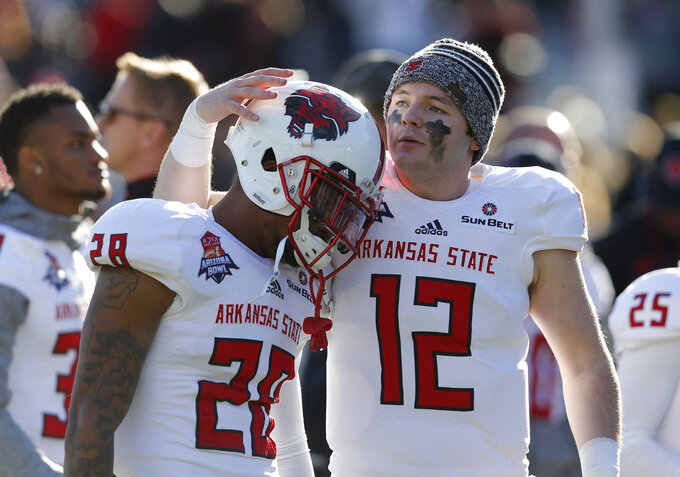 Arkansas State defensive back Brandon Byner (28) and Nathan Page react after losing to Nevada 16-13 in overtime of the Arizona Bowl NCAA college football game Saturday, Dec. 29, 2018, in Tucson, Ariz. (AP Photo/Rick Scuteri)