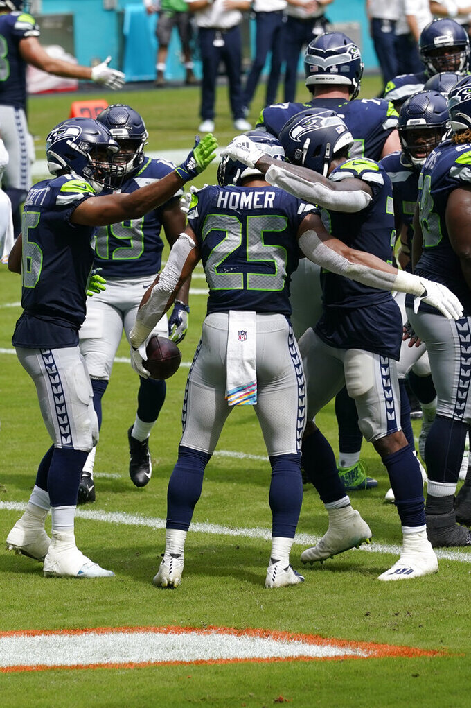 Teammates congratulate Seattle Seahawks running back Travis Homer (25) after Homer scored a touchdown during the first half of an NFL football game against the Miami Dolphins, Sunday, Oct. 4, 2020, in Miami Gardens, Fla. (AP Photo/Lynne Sladky)